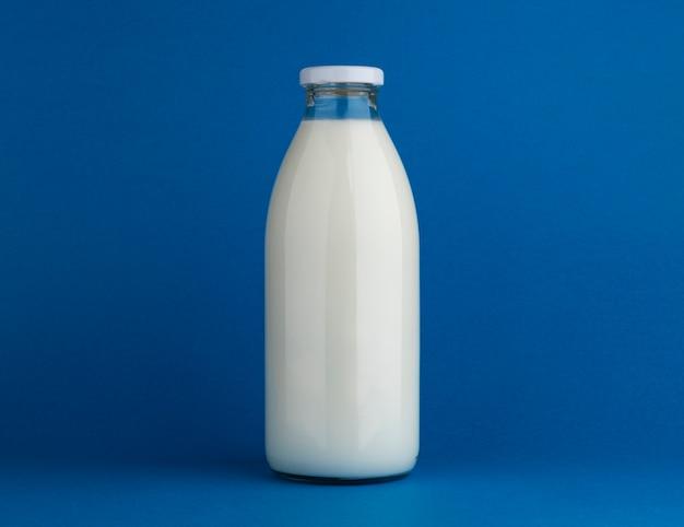 Glass milk bottle mock up on blue background