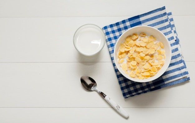Glass of milk next to bowl of cereals on cloth