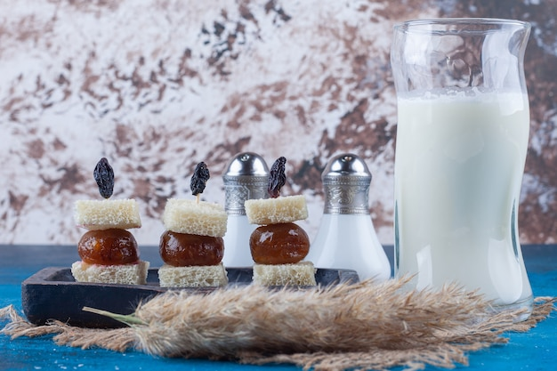 A glass of milk next to bread in a skewers on a wooden plate, on the blue table.