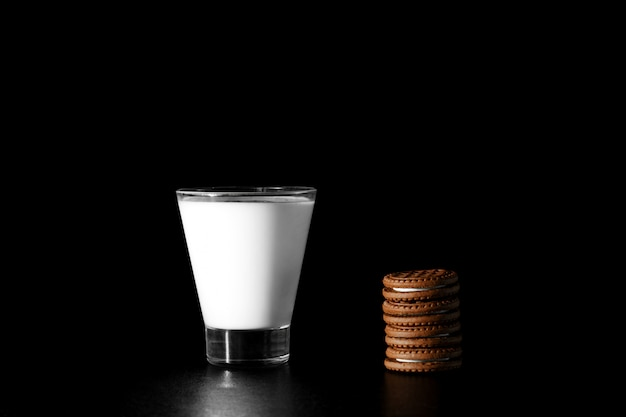 Glass of milk and chocolate cookies on black