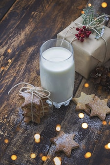 Glass of milk and christmas cookies on brown wooden table with christmas lights