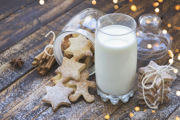 Glass of milk and cookies on brown wooden table with christmas lights