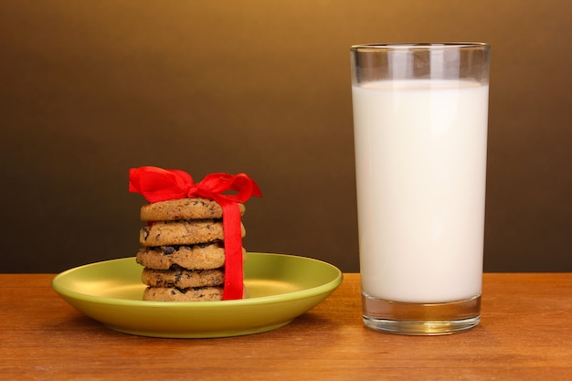 Glass of milk and cookies on wooden table on brown surface