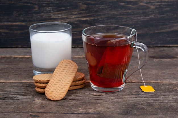 Glass of milk, cup og black tea and cookie on a wooden table