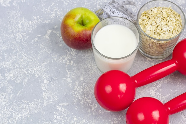 A glass of milk and a glass of oat flakes (rolled oats). apple with measuring tape and dumbbells.
