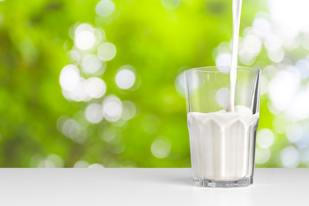 A glass of milk on greenery