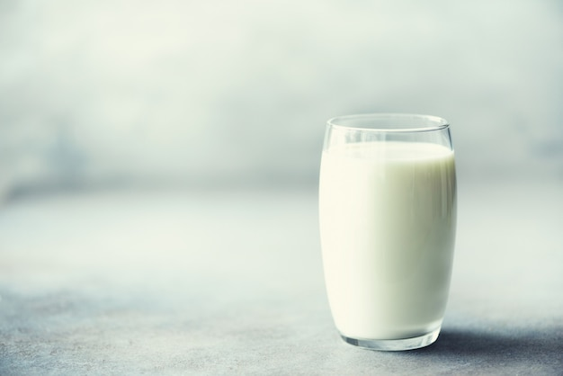 Glass of milk on grey concrete background woth copy space.
