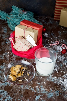 Glass of milk and homemade cookies with chocolate to santa on table, christmas decorations,