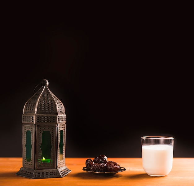 Glass of milk near saucer with sweet prunes and lantern