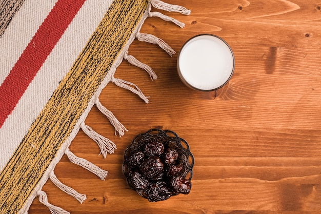 Glass of milk near saucer with sweet prunes and mat