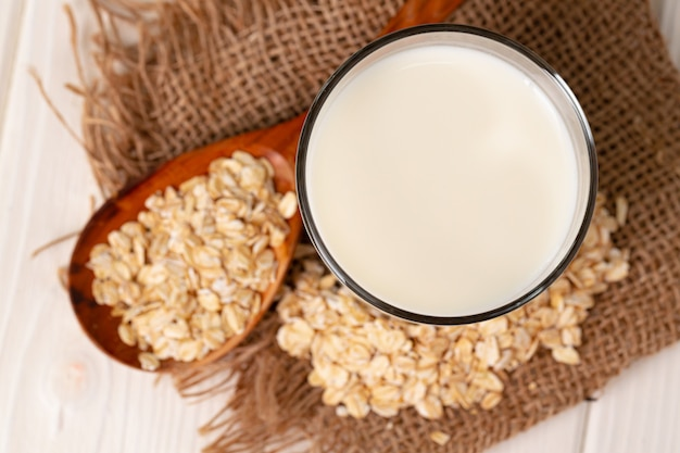 Glass of milk and oat flakes on wooden table close up