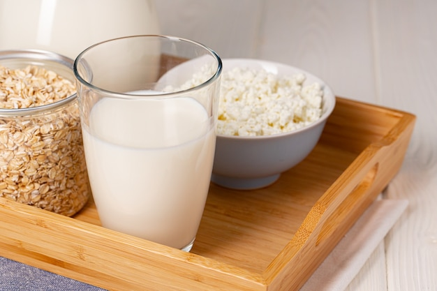 Glass of milk and oat flakes on wooden table