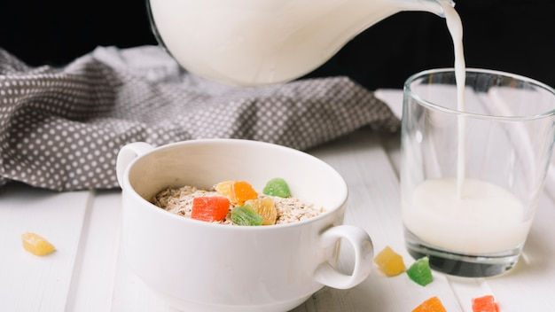 Glass of milk and oatmeal with jelly candies on table