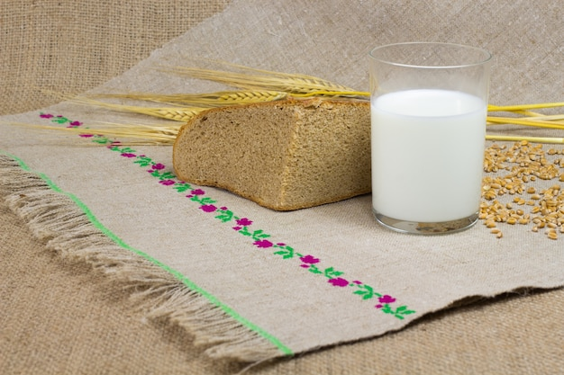 A glass of milk, a quarter of bread, wheat ears. woven cloth made of hemp