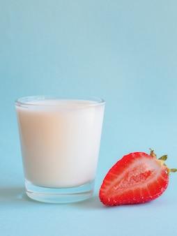 Glass of milk and ripe strawberries