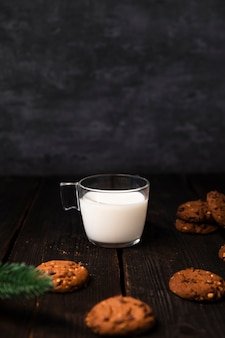 Glass of milk surrounded by tasty cookies