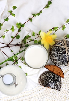 Glass of milk and sweet cakes with ginger and vanilla rustic home cooking white background