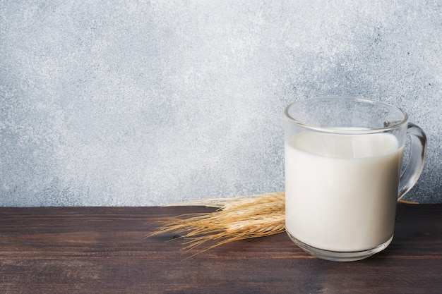 Glass of milk and wheat branches on rustic background