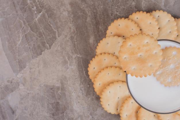 Un bicchiere di latte con biscotti sul tavolo di marmo