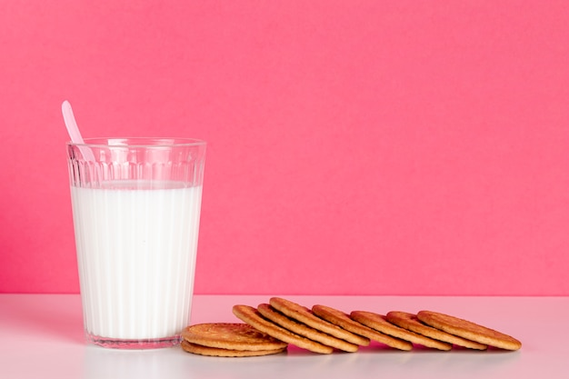 Glass of milk with delicious biscuits front view