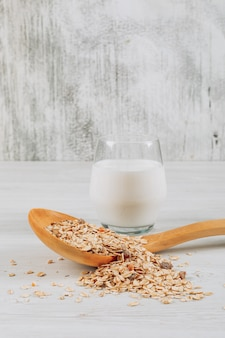 Glass of milk with oats in wooden spoon side view on a white wooden background
