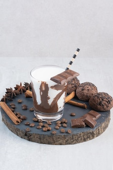 Glass of milk with straw, chocolate and cookies on wooden piece