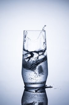 Glass of mineral sparkling water with ice on blue