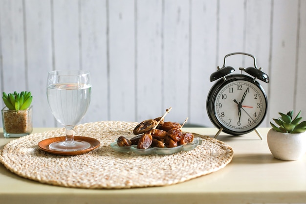 Glass of mineral water and dates with alarm clock showing 6 oclock for iftar time