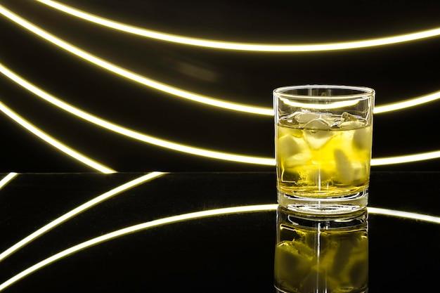 透明な暗いテーブルの上に飲み物と氷を入れたガラスの霧のかかったガラス、光のまぶしさ、光を描きます。テキスト用の空き容量。ウイスキー、ブランデーのグラス