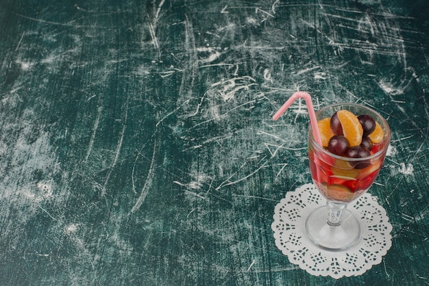 Glass of mixed fruit juice on marble table.