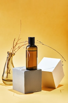 Glass mock up bottle of shampoo or conditioner of body care cosmetics on geometric shapes and dried branch. natural eco friendly organic cosmetic spa beauty concept.