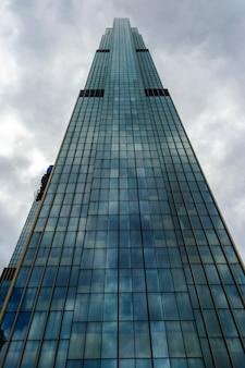 관점보기에서 어두운 구름과 폭풍우 치는 하늘 반대 유리 현대 마천루 건물