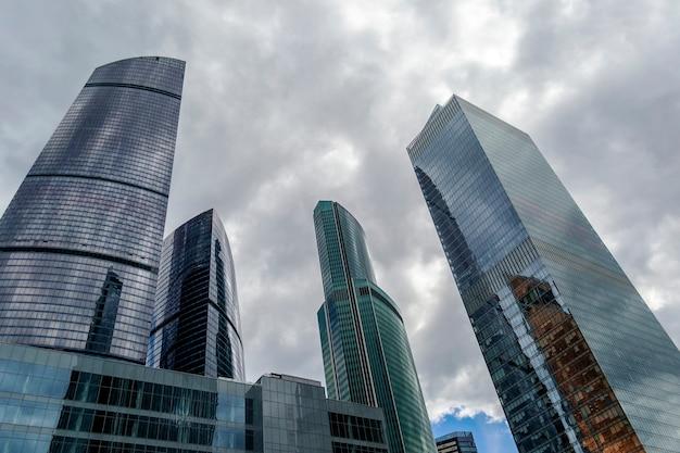 어두운 구름과 폭풍우 치는 하늘 반대 유리 현대 마천루 건물