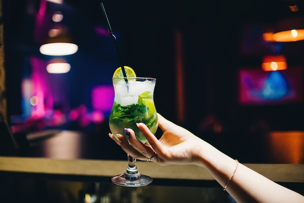 Glass of mojito cocktail in female hand with lime and mint