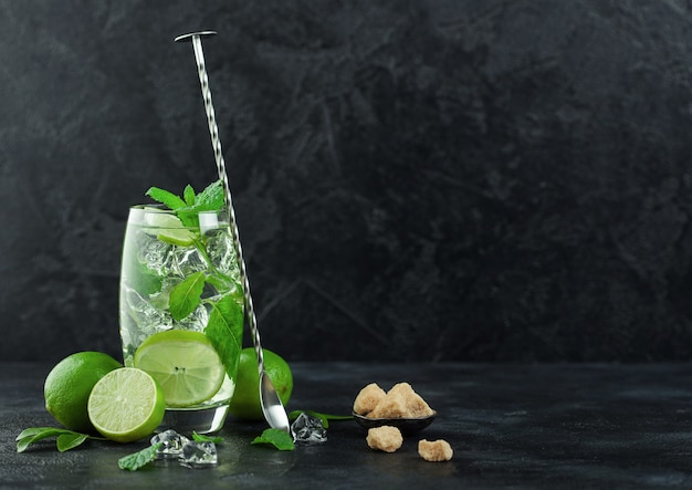 Glass of mojito cocktail with ice cubes mint and lime on black background