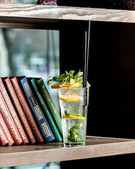 A glass of mojito drink placed next to books