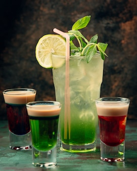 A glass of mojito with three colorful shots around