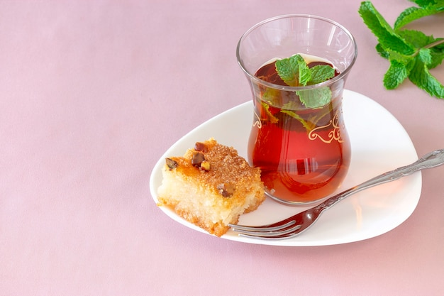 Glass of moroccan mint tea with basbousa (namoora) traditional arabic semolina cake with almond nut and syrup. copy space. selective focus. pink background.