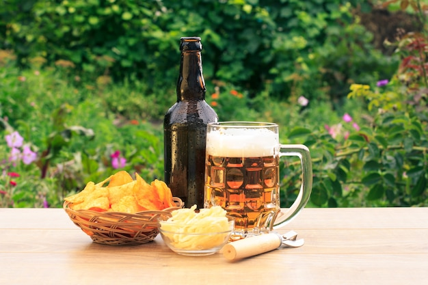 Glass mug of beer and bottle of beer on wooden table with potato chips in wicker basket, dried squid in bowl and  opener