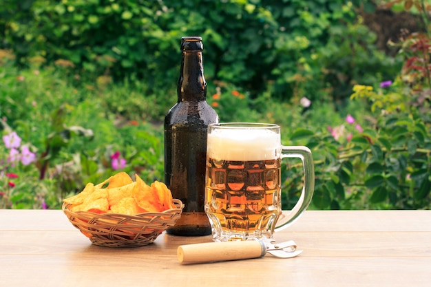 Glass mug of beer and bottle of beer on wooden table with potato chips in wicker basket and opener