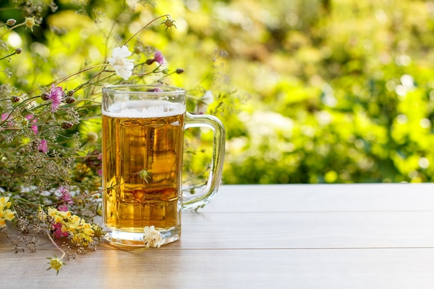 Glass mug of beer on wooden table with bouquet  of wildflowers on natural green blurred background