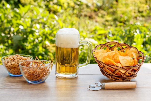 Glass mug of beer on wooden table with potato chips in wicker basket, peanuts and dried squid in bowls on natural green blurred background