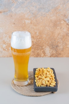 A glass mug of foam beer with fish shaped crackers on a stone background.