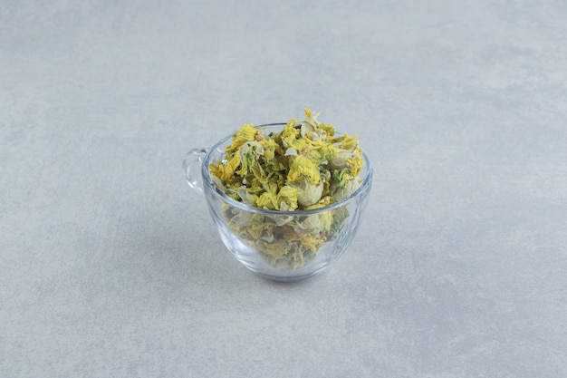 Tazza di vetro piena di fiori gialli in tavola di pietra.