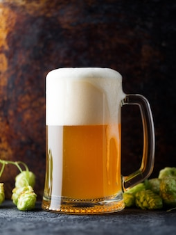 A glass mug of german wheat beer with a large foam layer