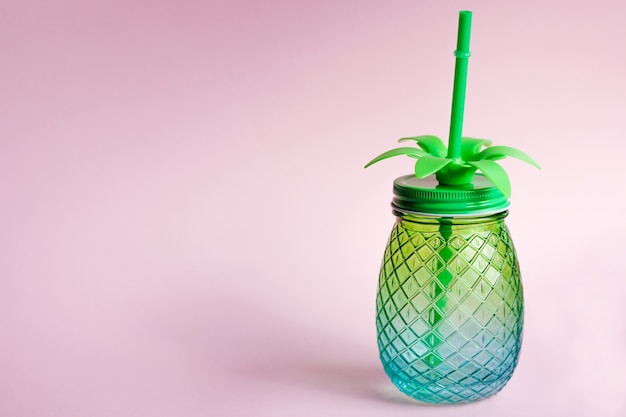 A glass mug or jar with a pineapple shaped tu. the concept of the spirit of summer, vacation