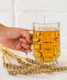 흰색 바탕에 보리 귀가 있는 여성의 손에 맥주 한 잔.