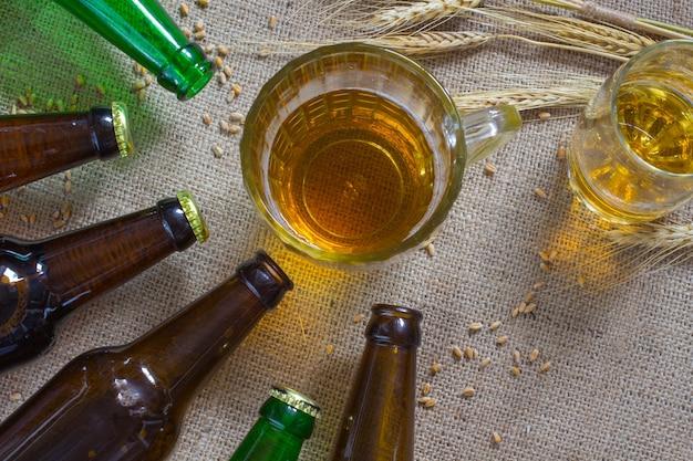 Стеклянная кружка пива. колоски пшеницы на мешковине. стеклянные бутылки.