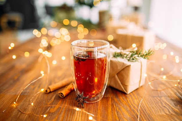 ガーランドライトが付いている木製のお祝いのテーブルにスターアニスと紅茶のガラスのマグカップ