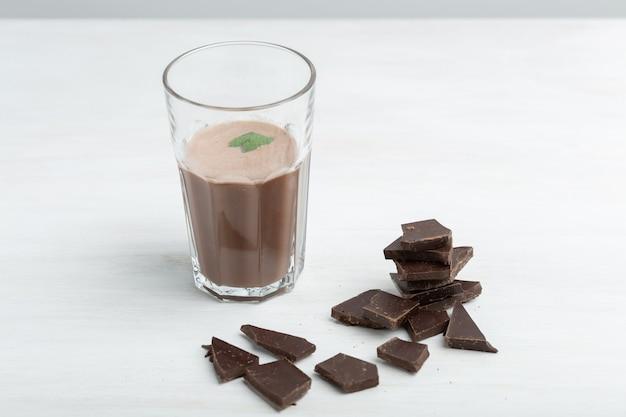 단백질 초콜릿 쉐이크와 함께 유리 머그잔은 흰색 테이블에 단백질 패킷의 배경을 의미합니다. 스포츠 영양 개념.